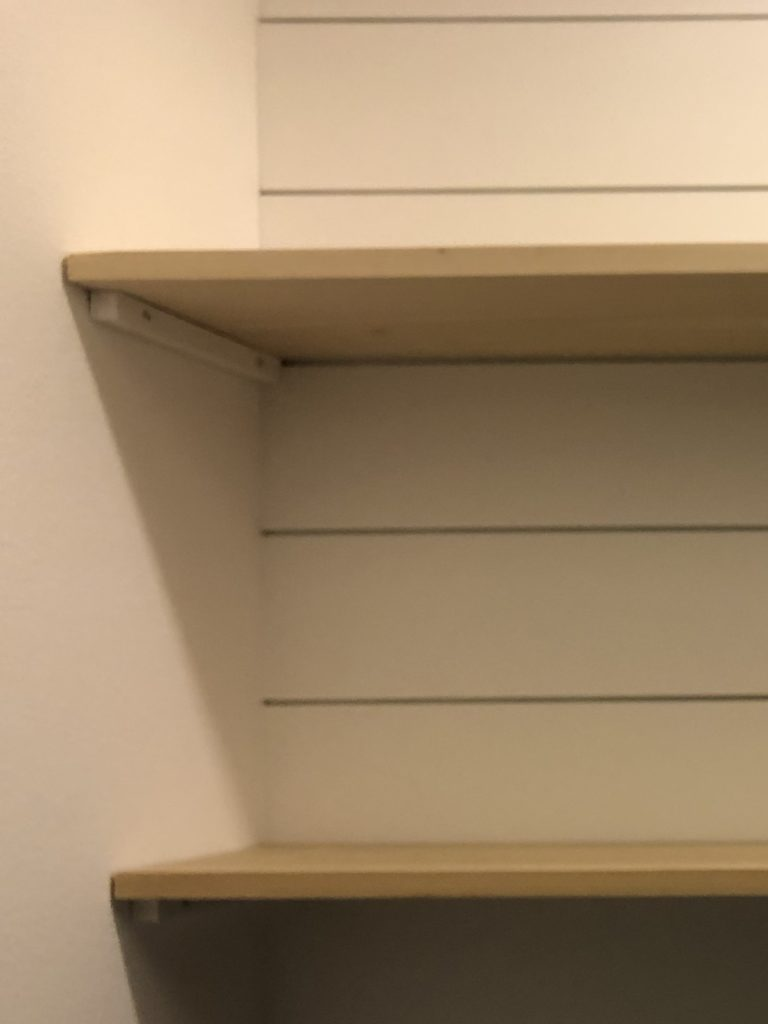 Shelf hack. Showing a closeup of how we secured the shelves between two walls using 1x1 wood pieces.