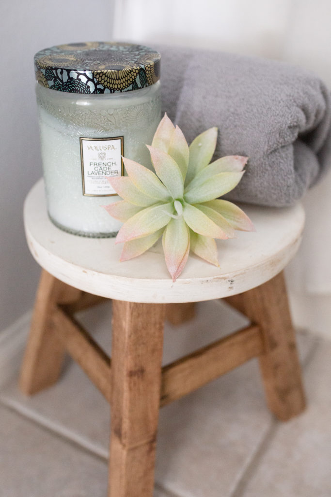 Bathroom makeover - Little foot stool from Hobby that has white top and wooden legs with candle, faux succulent, and towel for decor.