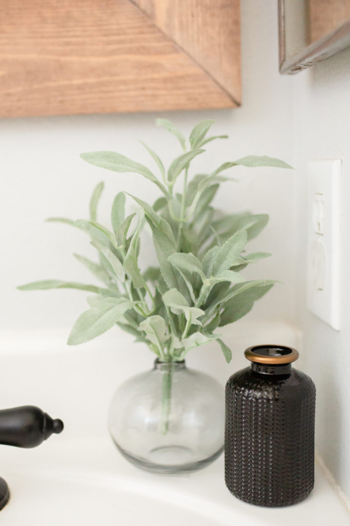 Bathroom makeover - Grey vase and black bottle with Faux greenery from Hobby lobby on vanity for decor.