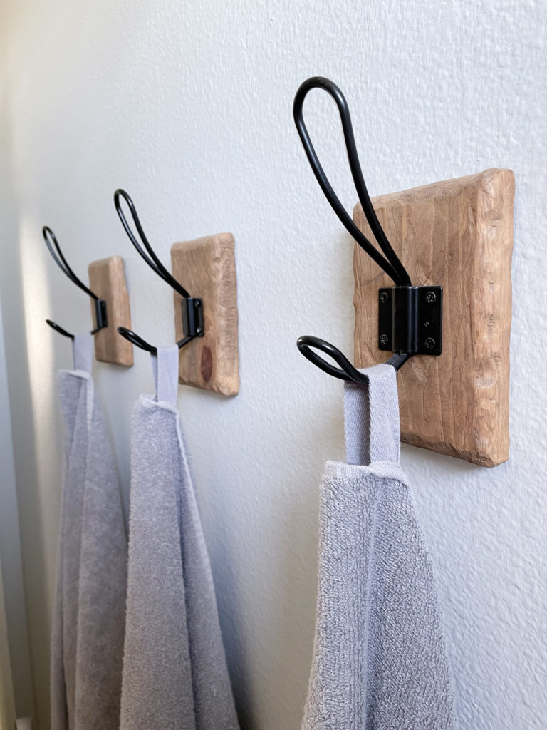 Bathroom makeover - Closeup of Farmhouse Towel Hooks with DIY rustic wood backing