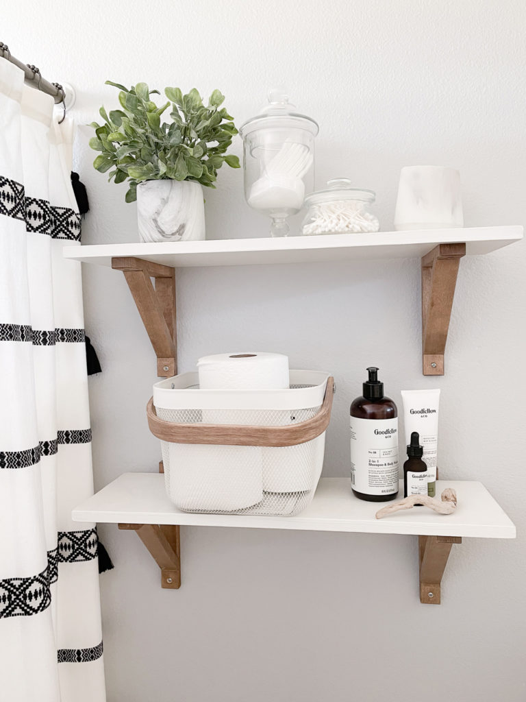 Farmhouse styled bathroom shelves with marbled pot faux plant, apothecary jars, ikea basket and Goodfellow cosmetics.