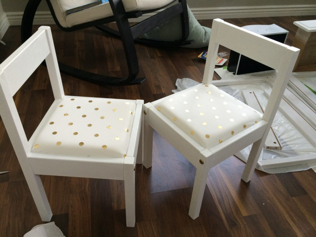 Ikea LATT chair hack with white paint, and white & gold polka dot cushions.