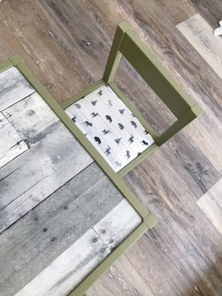 Ikea table and chair for boys room with 'Olive Grove' by BM paint, white 'woodland animal' fabric cushions, and 'wood' wallpaper tabletop.