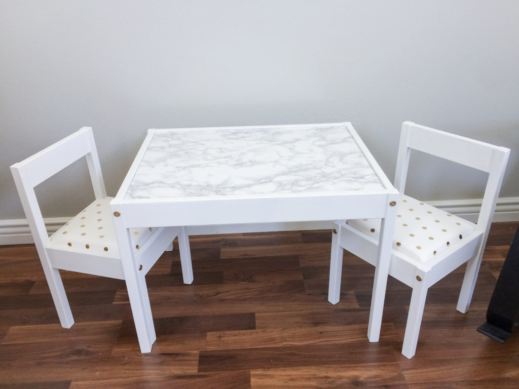 Ikea LATT table and chair hack for girls room with white paint, white & gold polka dot cushions, and marble tabletop.