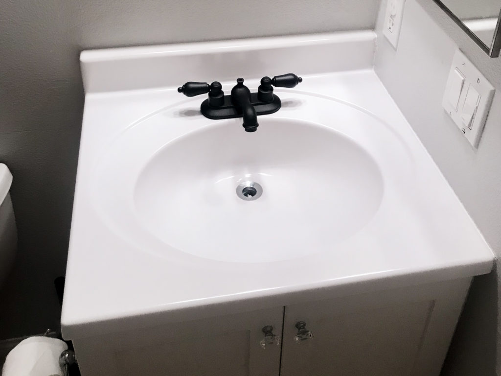 Vanity makeover with white Appliance Epoxy Spray. Faucet sprayed with matte black spray paint too.