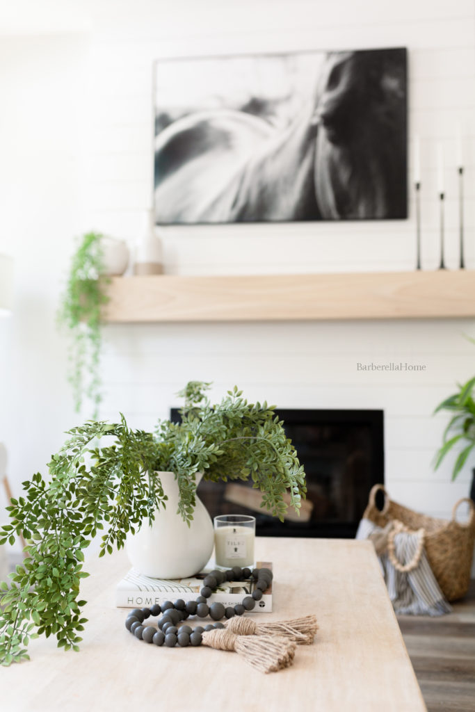 Pull back view of decor on coffee table with fireplace in the background. White ceramic pot (from walmart) with greenery (from hobby lobby) hanging over a coffee book (Home body by Joanna Gaines), candle (tides candle), and grey wood beads (from Hobby lobby).