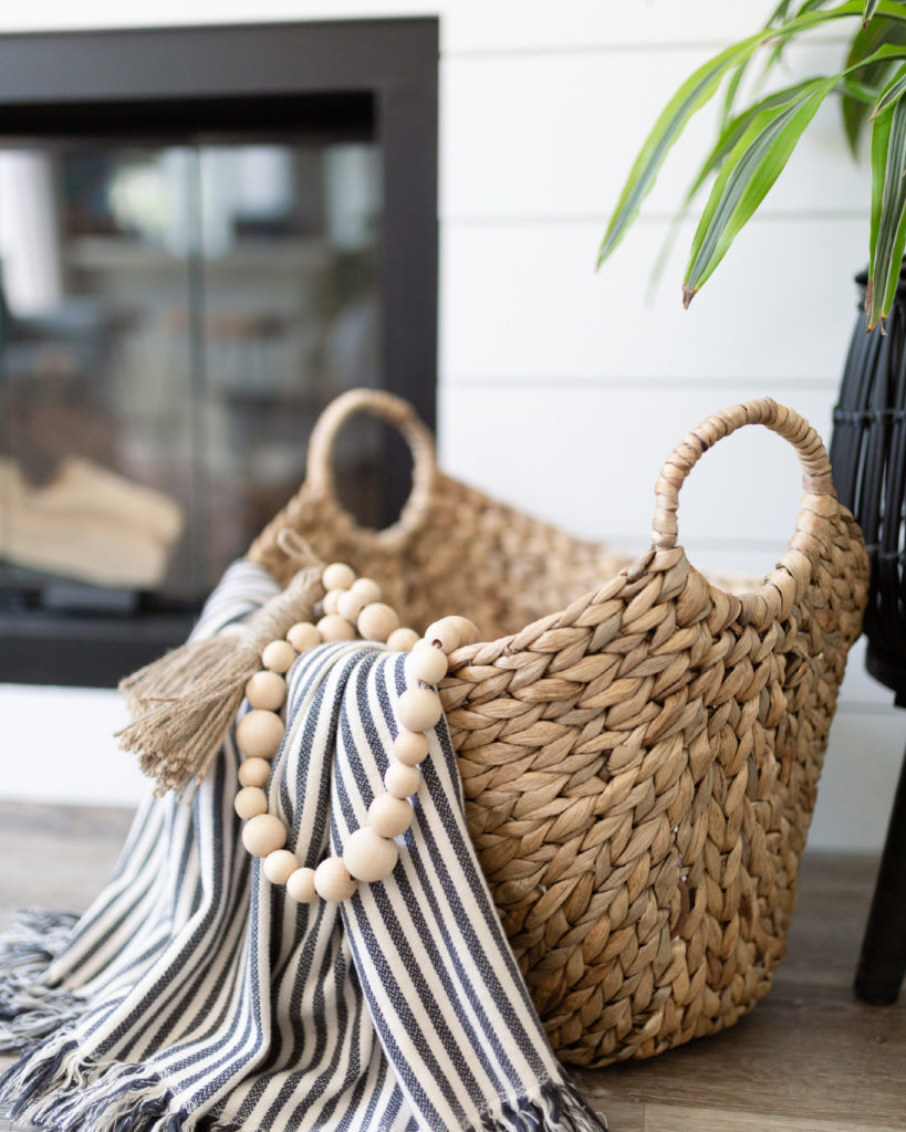 Closeup view of the decor in front of the fireplace. A boat basket (from Walmart) with striped throw (from Ikea) and wooden beads (from Hobby lobby)