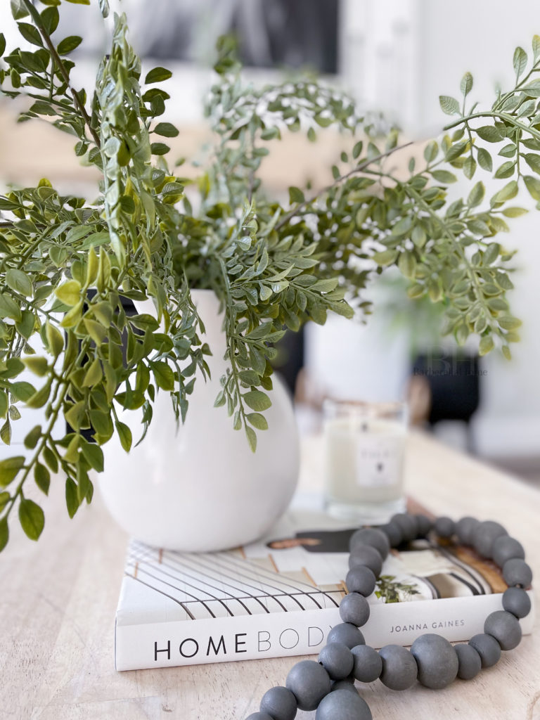 Closeup of decor on coffee table. White ceramic pot (from walmart) with greenery (from hobby lobby) hanging over a coffee book (Home body by Joanna Gaines), candle (tides candle), and grey wood beads (from Hobby lobby).