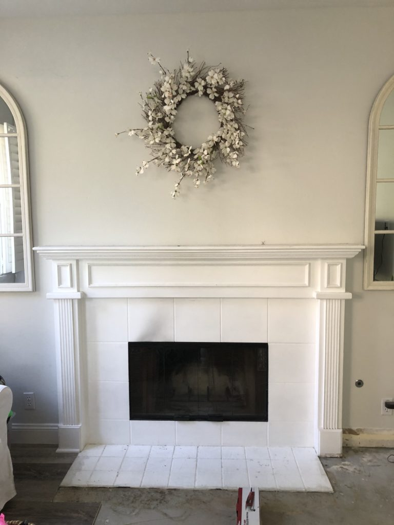 Preview of fireplace and mantle before remodel - builder grade trim and moulding with outdated white tile hearth.