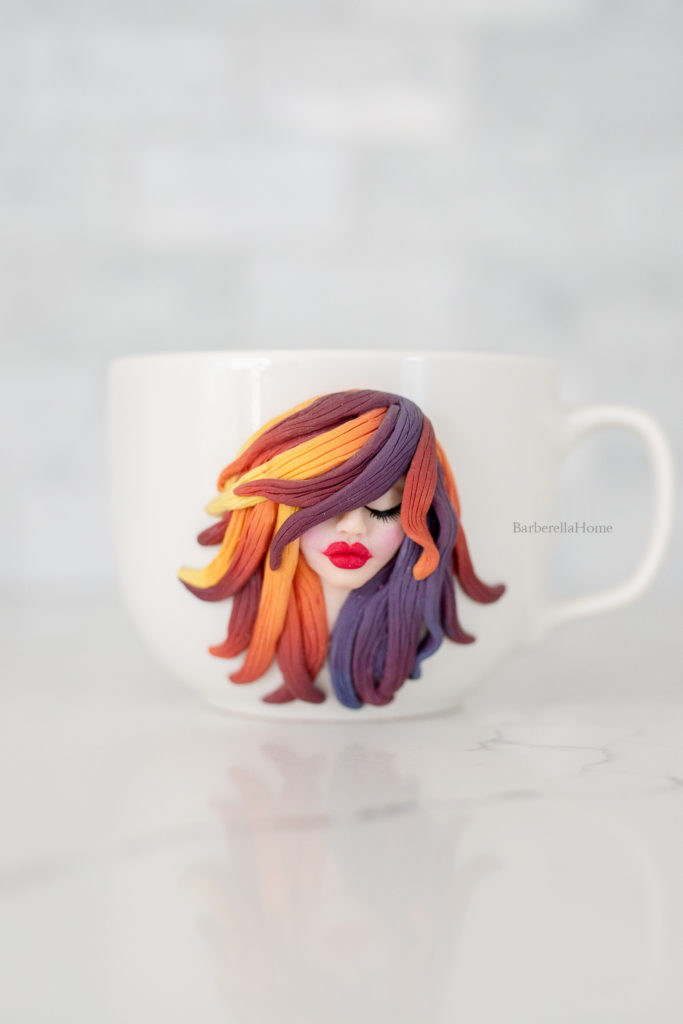 mug art: 3D image of woman's face made out of polymer clay with colorful ombre hair.